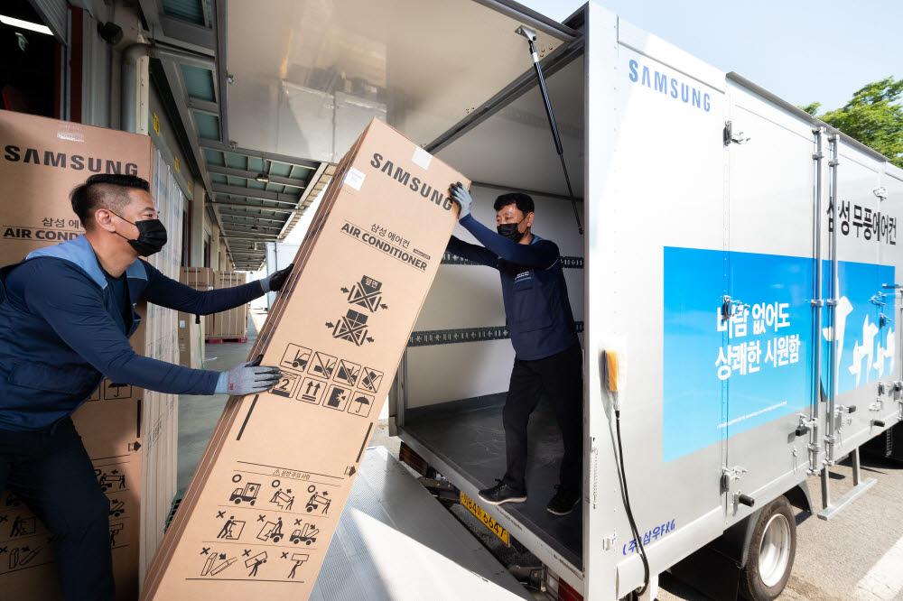 경기도 수원시 영통구에 위치한 삼성전자로지텍 수원센터 물류창고에서 담당자들이 삼성 비스포크 무풍에어컨을 배송하기 위해 차량에 싣고 있다.