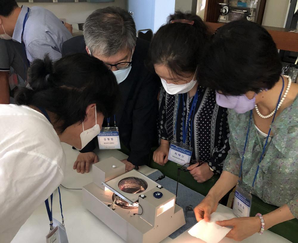 지난해 직무연수 당시 전국에서 모인 교사들이 안개상자 체험으로 방사선을 관찰하는 모습.