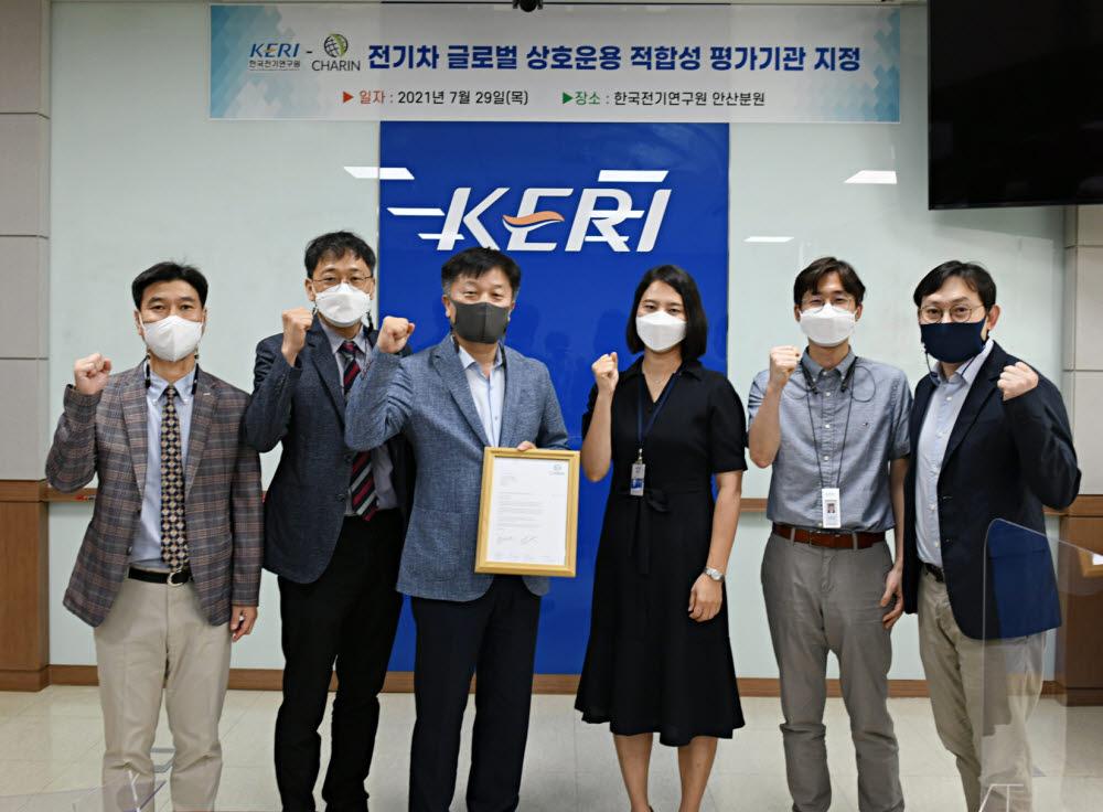 유동욱 KERI 원장 직무대행(왼쪽 세번째)이 이민정 차린 코리아 이사(왼쪽 네번째)로부터 전기차 글로벌 상호운용 적합성 평가기관 지정서를 받고 기념촬영했다.