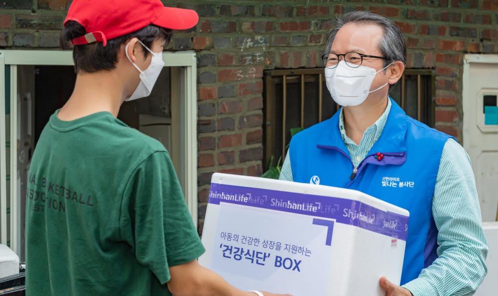 성대규 신한라이프빛나는재단 이사장(오른쪽)이 서울 용산구 결식 우려 아동에게 직접 건강식단이 담긴 상자를 전달했다.