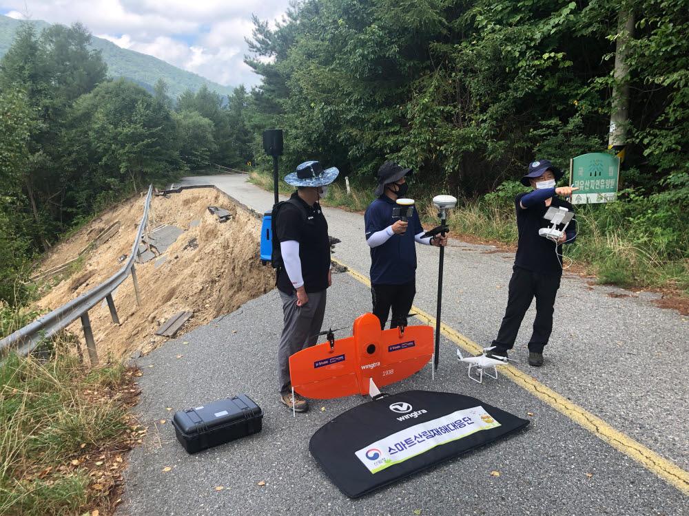 산림청 스마트산림재해대응단 직원들이 첨단장비를 활용해 산사태피해지를 조사하고 있다.