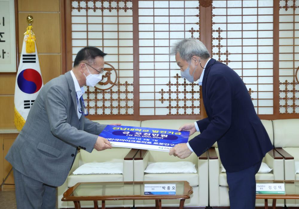 박종오 한국마이크로의료로봇연구원장(왼쪽)이 정성택 전남대 총장에게 발전기금 증서를 전달하고 있다.
