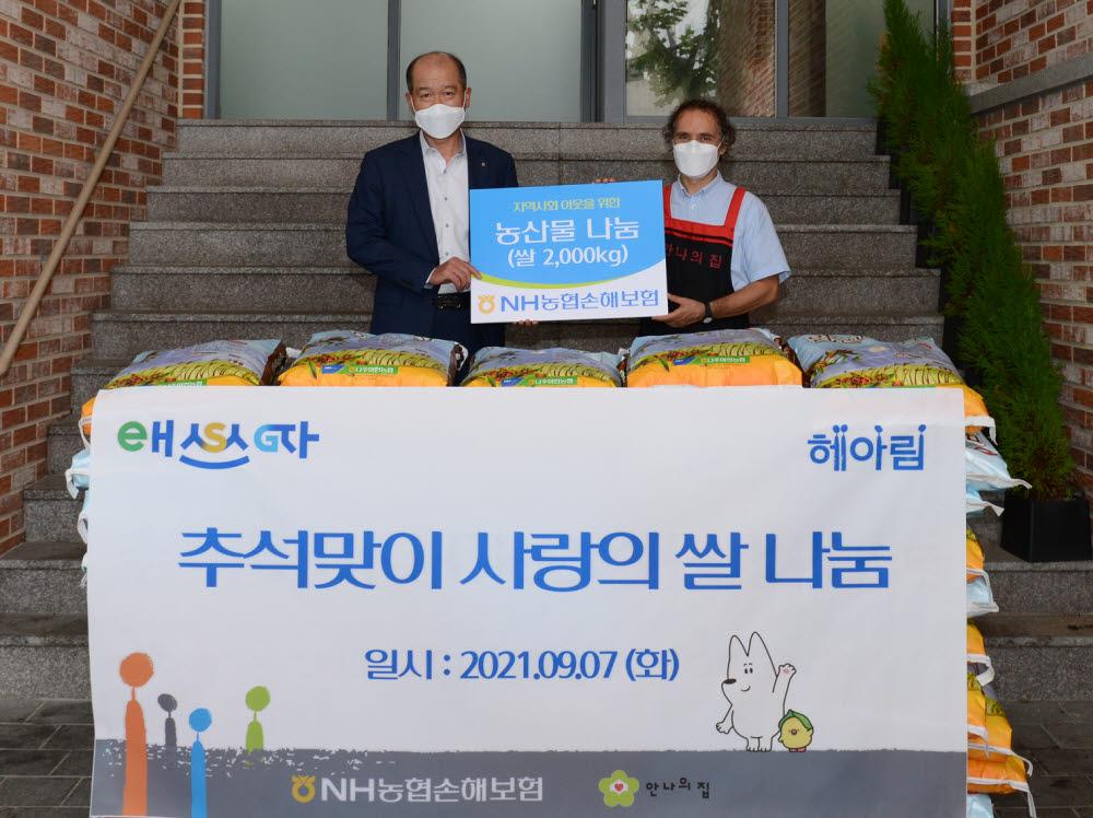 최창수 NH농협손해보험 대표이사(왼쪽)와 김하종 안나의 집 신부가 농산물 나눔 전달식을 마치고 기념촬영했다.