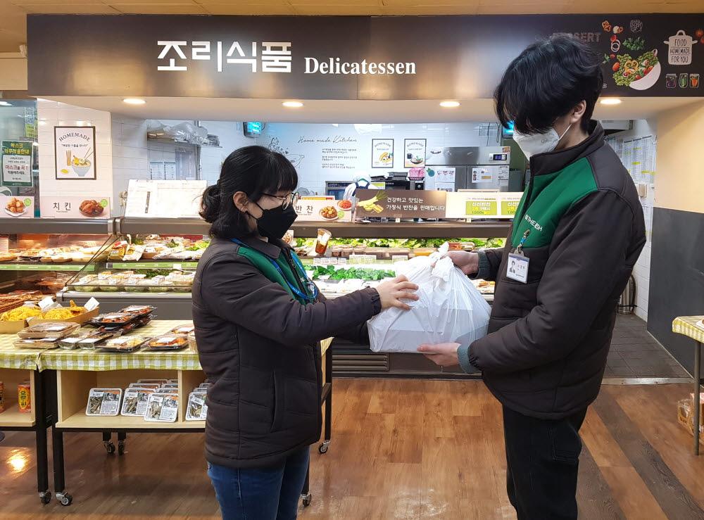 GS더프레시 직원이 온라인 주문 상품을 배송직원에게 전달하고 있다.