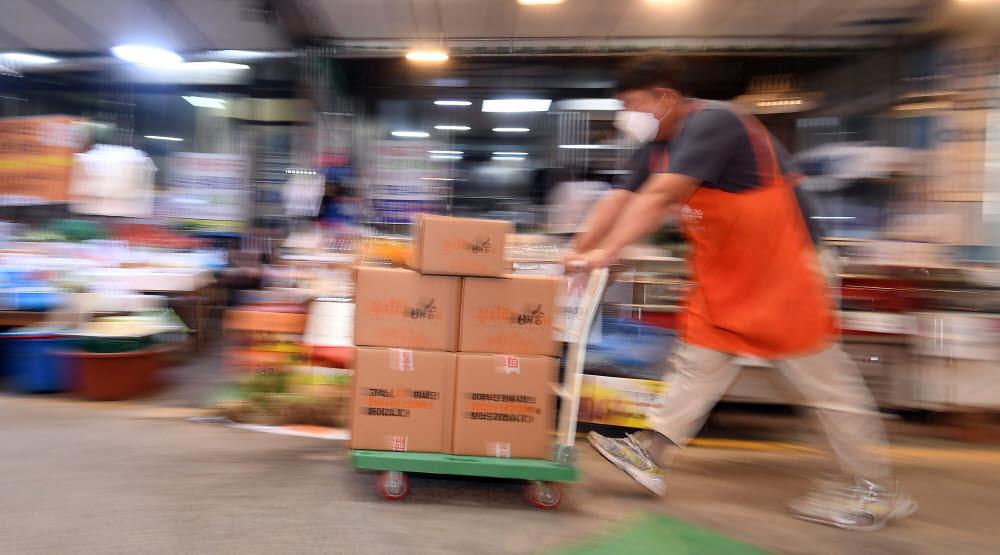 상인이 소비자에게 배송할 상품을 나르고 있다.
