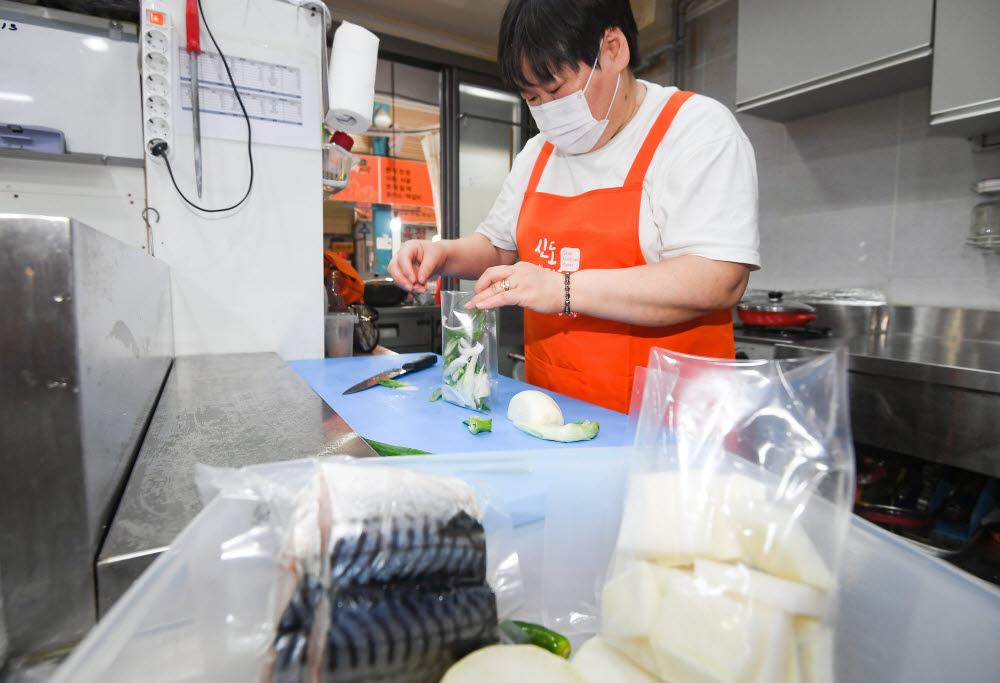 한 상인이 고등어조림 밀키트를 제작하고 있다.