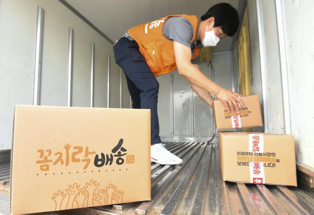 신도꼼지락시장 골드체인 배송차량 기사가 배송할 상품을 정리하고 있다.