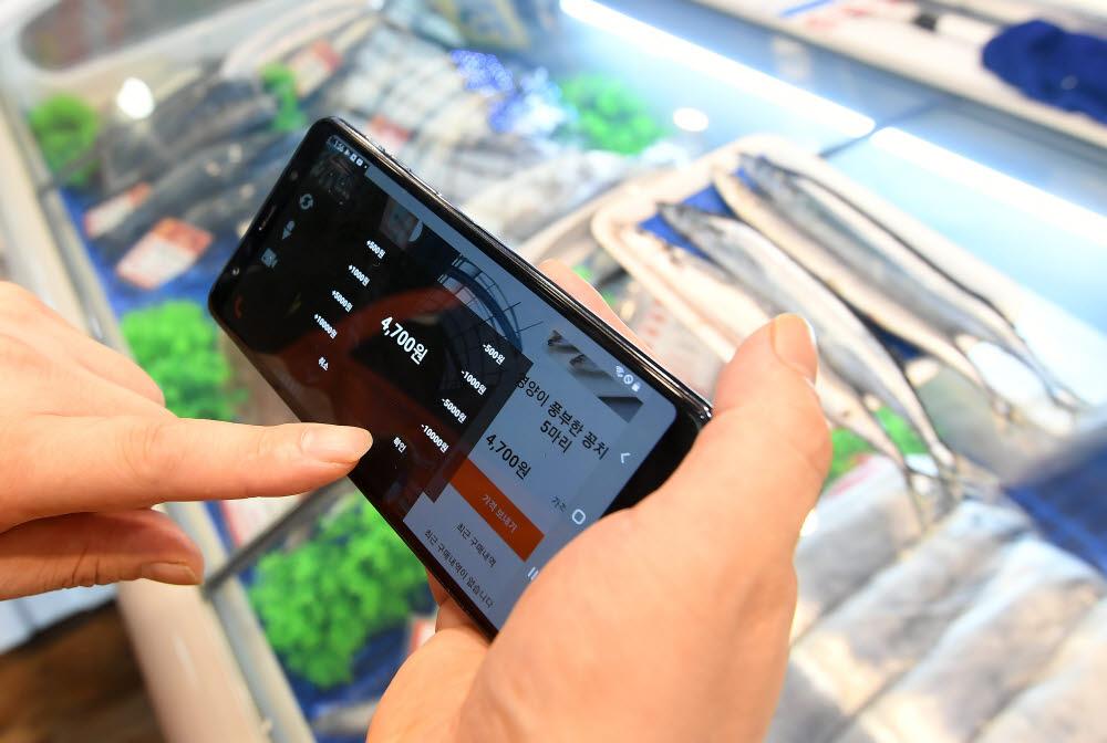 상인이 스마트오더 애플리케이션 꼼지락배송으로 소비자와 가격흥정을 하고 있다.