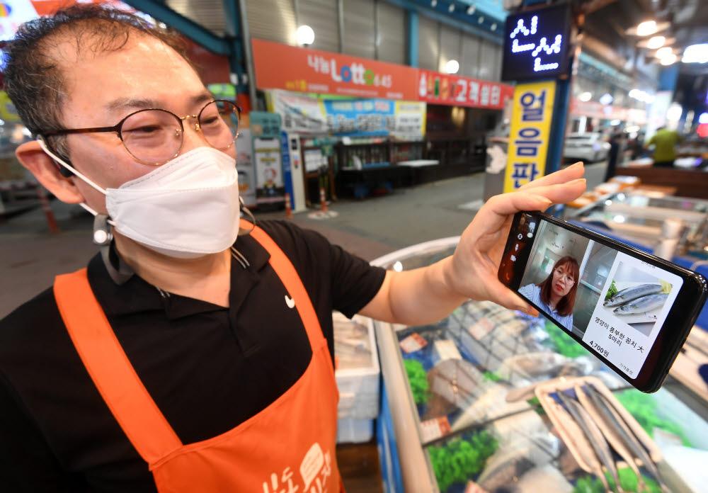 한 상인이 소비자와 꼼지락배송 앱을 이용해 영상통화를 하며 상품을 판매하고 있다.