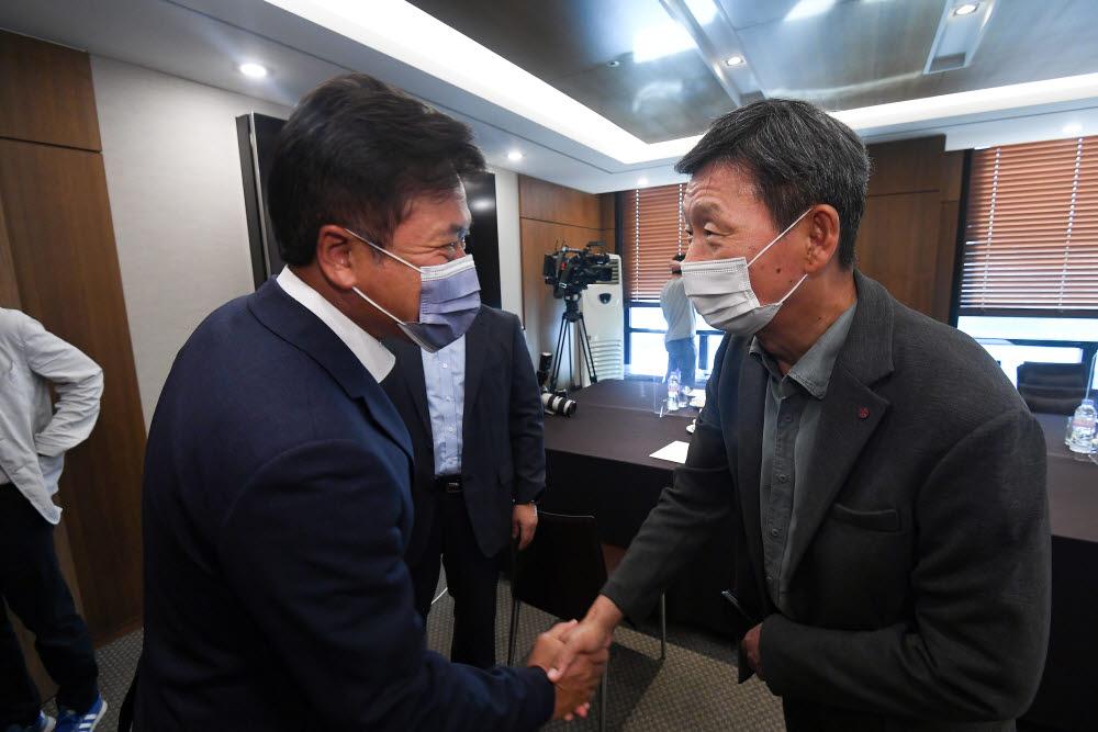 박정호 SK텔레콤 대표(왼쪽)와 황현식 LG유플러스 대표가 악수하고 있다.