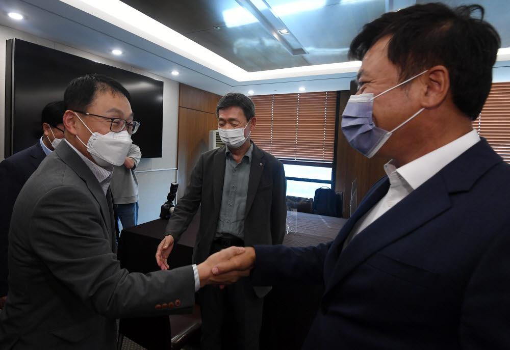 구현모 KT 대표(왼쪽)와 박정호 SK텔레콤 대표가 악수하고 있다.