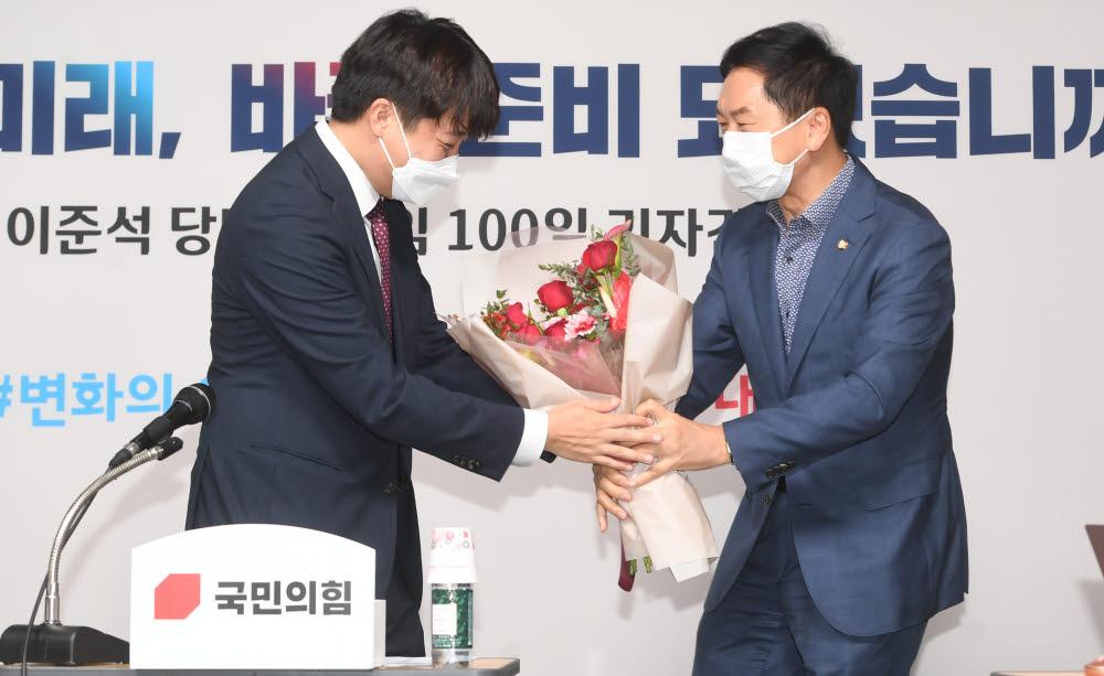 국민의힘 이준석 대표(왼쪽)가 17일 서울 여의도 국민의힘 중앙당사에서 열린 취임 100일 기자간담회에서 김기현 원내대표로부터 축하를 받고 있다. 국회사진기자단