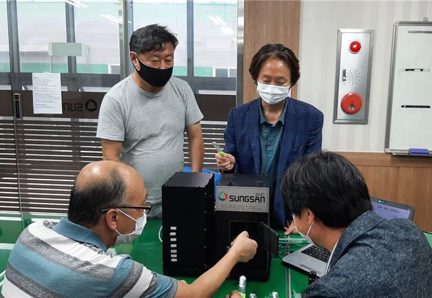 한국광기술원 연구원들이 소변 검사 장비를 시연하고 있다.
