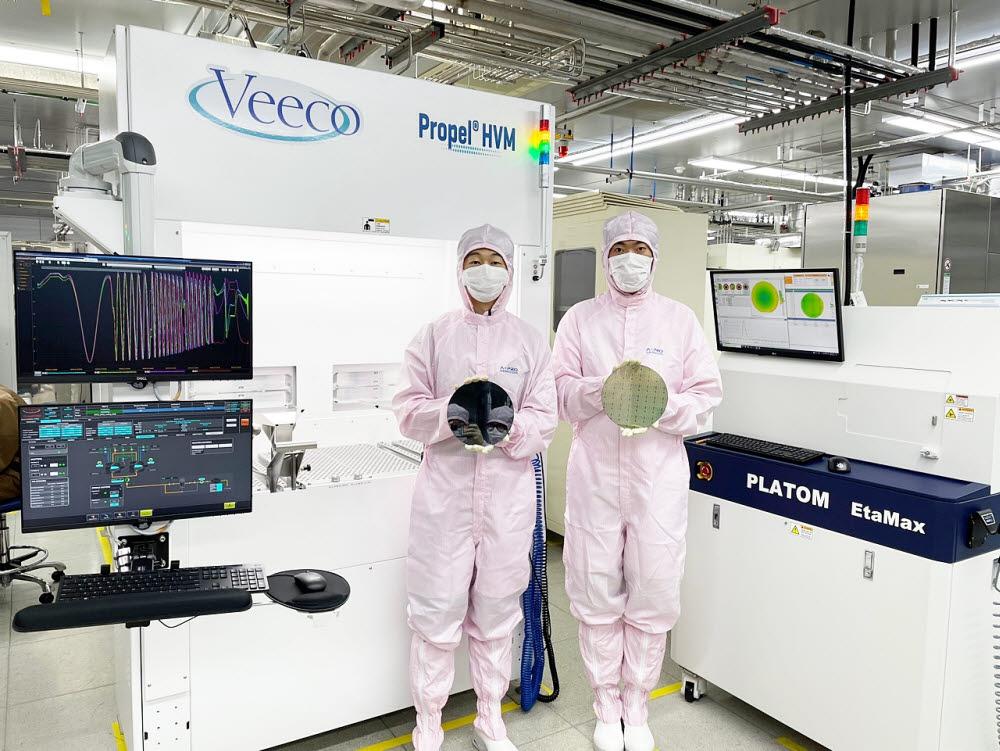 에이프로세미콘이 8인치 질화갈륨(GaN) 에피웨이퍼 양산을 개시했다. 에이프로세미콘 엔지니어가 8인치 GaN 웨이퍼 샘플을 들고 기념촬영했다.