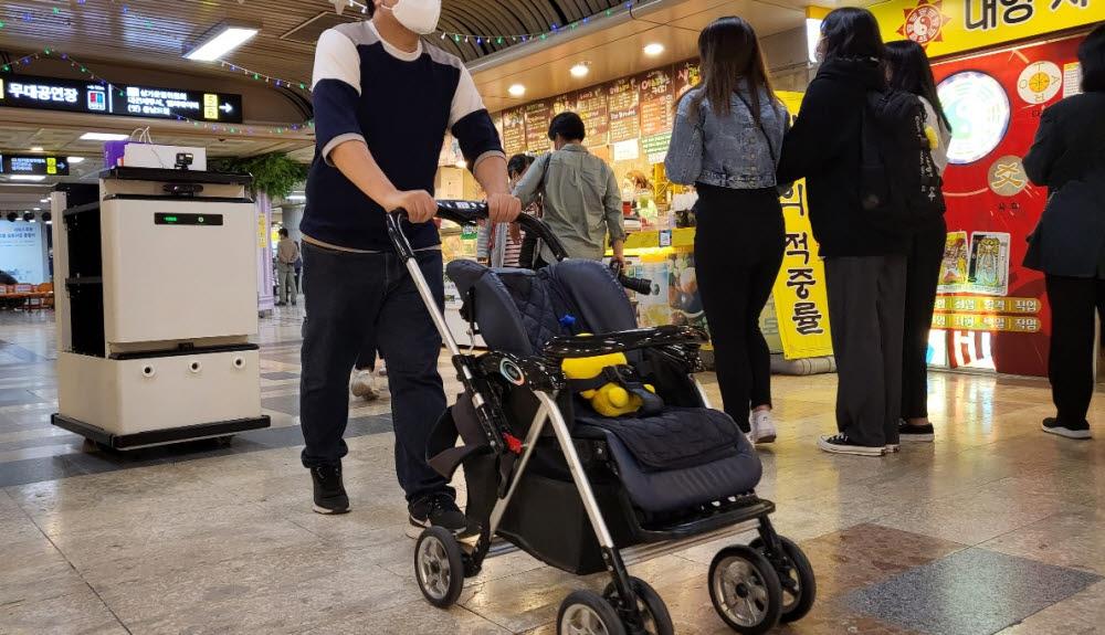 자율주행 로봇 전문기업 트위니(대표 천홍석·천영석)가 개발한 추종형 로봇 따르고가 출범식 시연 현장에서 유모차를 끌고 쇼핑하는 남성을 따라다니고 있다.