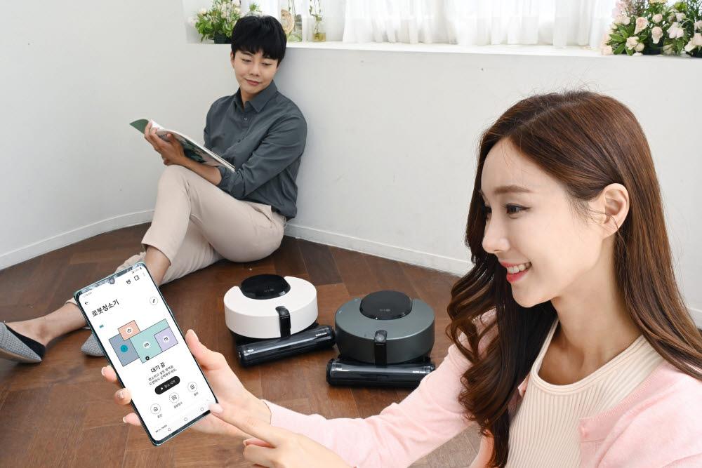 LG전자 모델이 LG 씽큐를 이용해 로봇청소기 코드제로 R9 오브제컬렉션을 작동하고 있다.