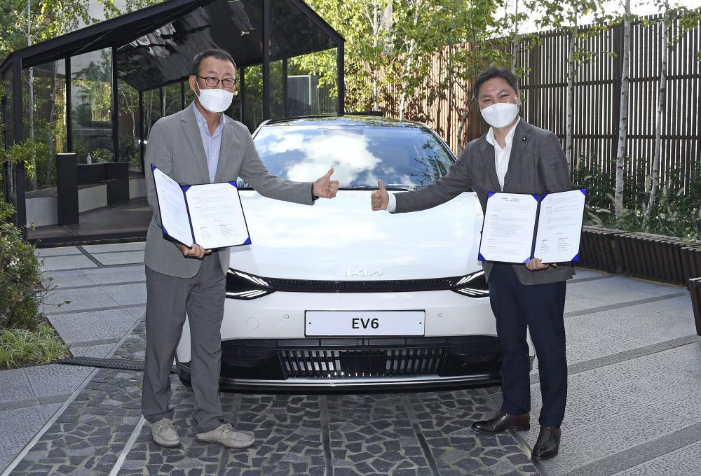 기아 판매사업부장 이한응 전무(왼쪽), 휴맥스 모빌리티 오영현 공동대표가 기념촬영을 하고 있다.